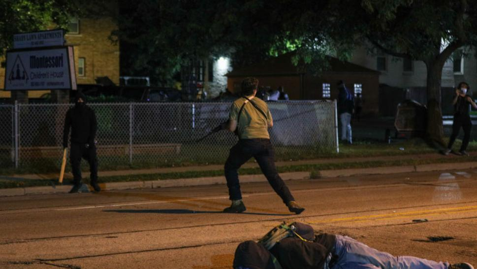 A man on the ground was shot in the chest as clashes between protesters and armed civilians who protect the streets of Kenosha against the arson during the third day of protests over the shooting of a black man Jacob Blake by police officer