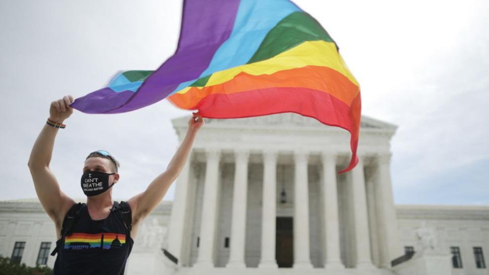Joseph Fons holding a Pride Flag in front of the U.S. Supreme Court building after the court ruled that LGBTQ people can not be disciplined or fired based on their sexual orientation, Washington, DC, June 15, 2020.