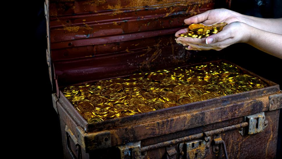 Lots Of Stacking Gold Coin In Lady Hand And Treasure Chest At Black Background - stock photo