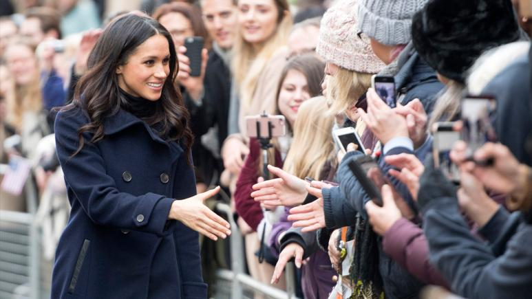Meghan Markle greets onlookers during her first royal visit.