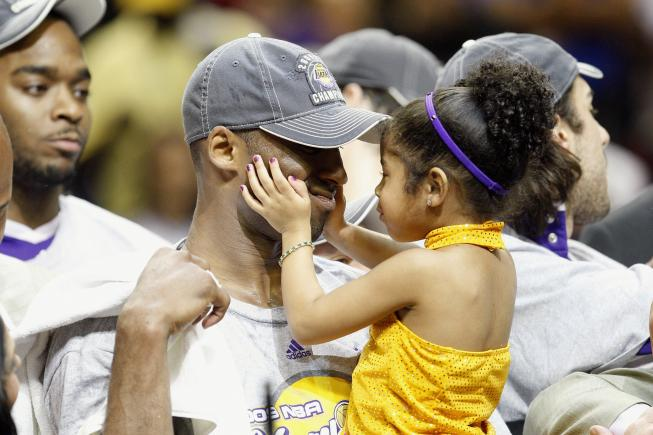 Kobe Bryant holds a 3-year-old Gianna on the court