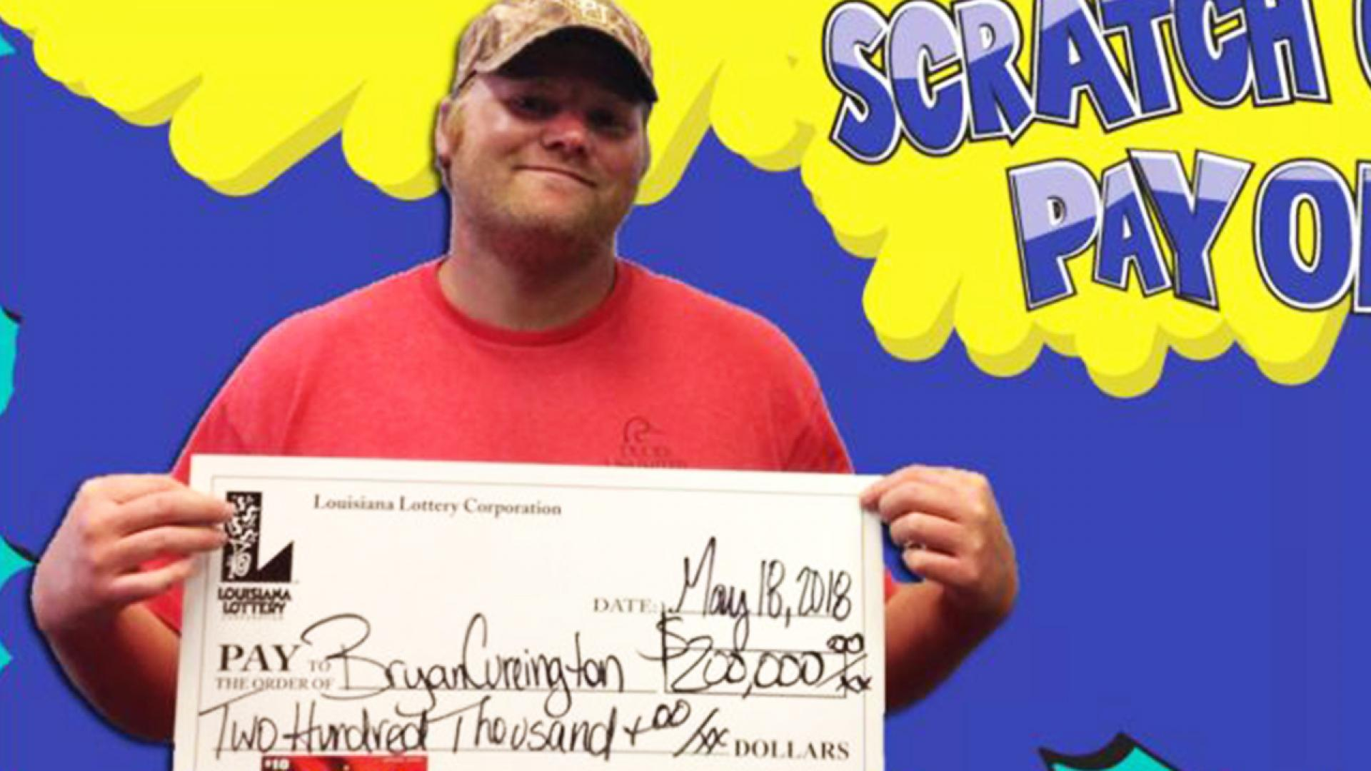 Bryan Cureington, 35, holds up his lottery payout.