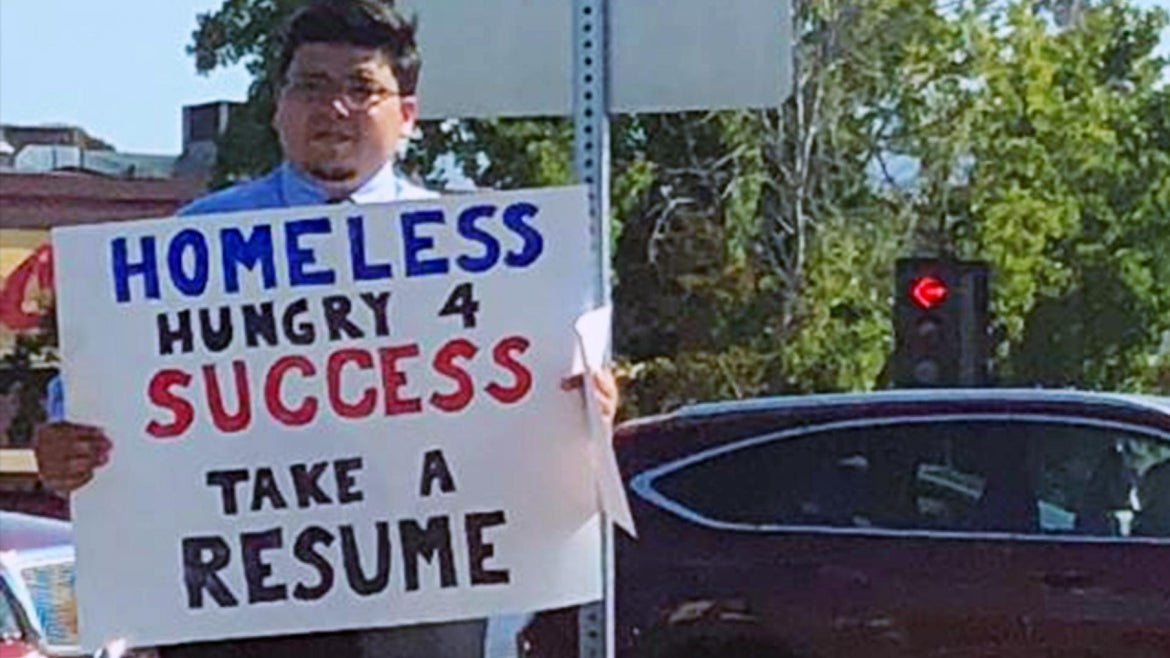 David Casarez, 26, holds up a sign while handing out his resume.