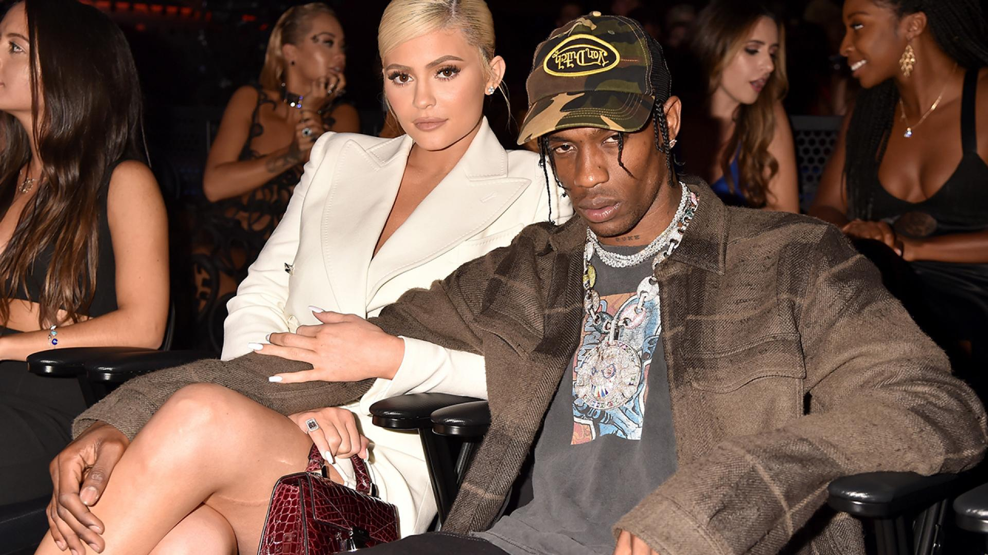 Kylie Jenner and Travis Scott sit side by side.