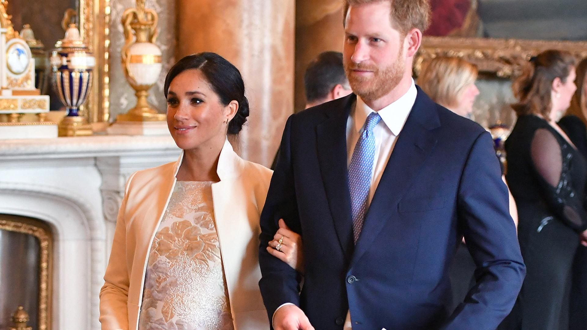 Meghan Markle and Prince Harry walk arm in arm at Buckingham Palace.