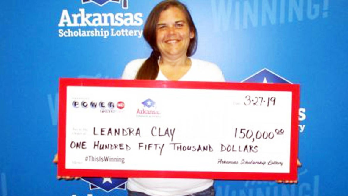 LeAndra Clay holds up her lottery winnings.