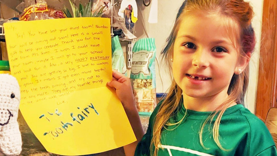 7-year-old Lily Sciulli holds up the letter the tooth fairy wrote back to her.