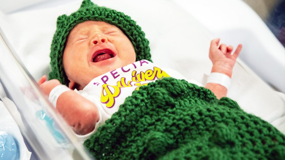 """Newborns were dressed in little pickle outfits to celebrate """"Pickleburgh,"""" Pittsburgh's annual pickle festival."""