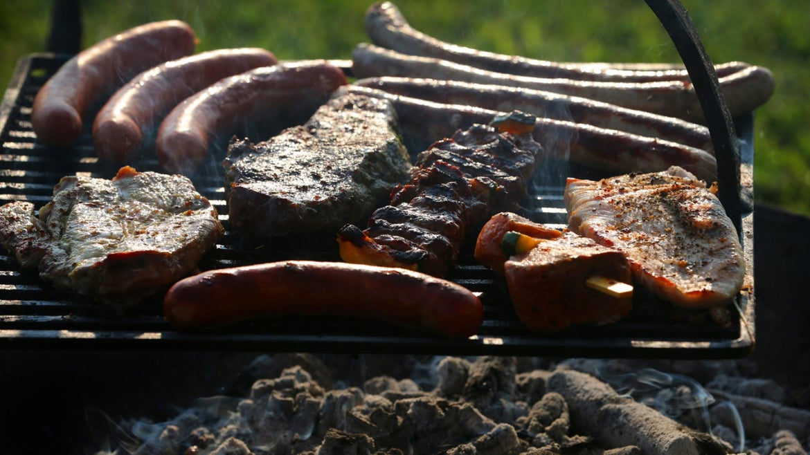 Various meat cooking on an open grill.