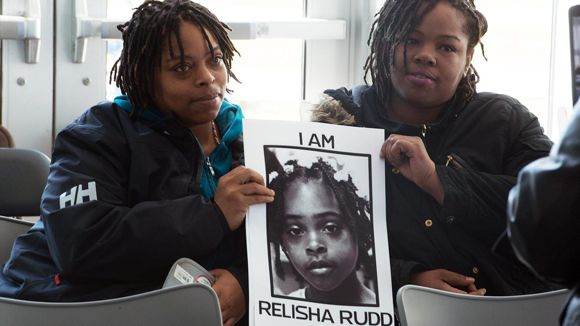 Relisha Rudd's mom, Shamika Young, left, and her god aunt, Kinnicia Williams, hold up her photo on a previous anniversary of her disappearance.