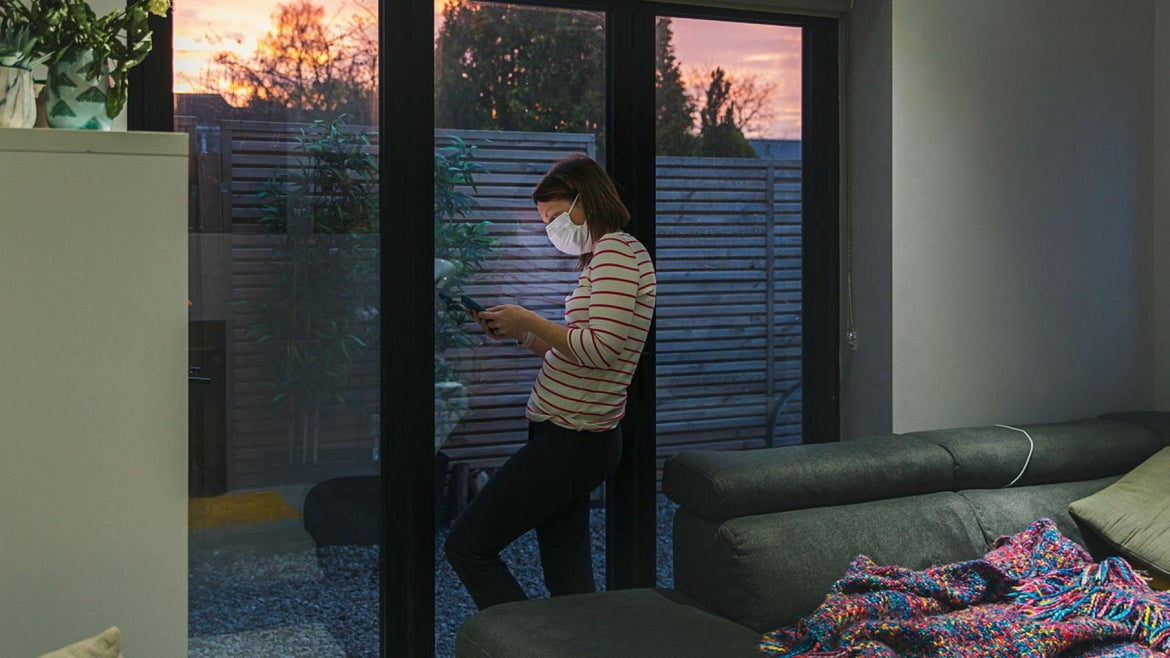 Woman in self isolation using smartphone by window - stock photo