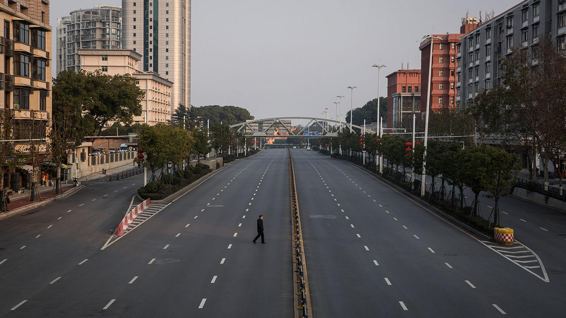 ) A man cross an empty highway road in Wuhan, Hubei province, China.