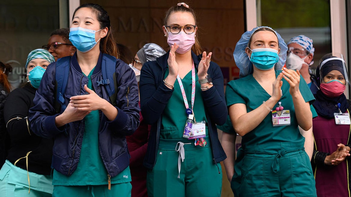 Medical workers stand outside NYU Langone Health hospital as people applaud to show their gratitude to medical staff and essential workers during the coronavirus pandemic on May 5, 2020 in New York City.
