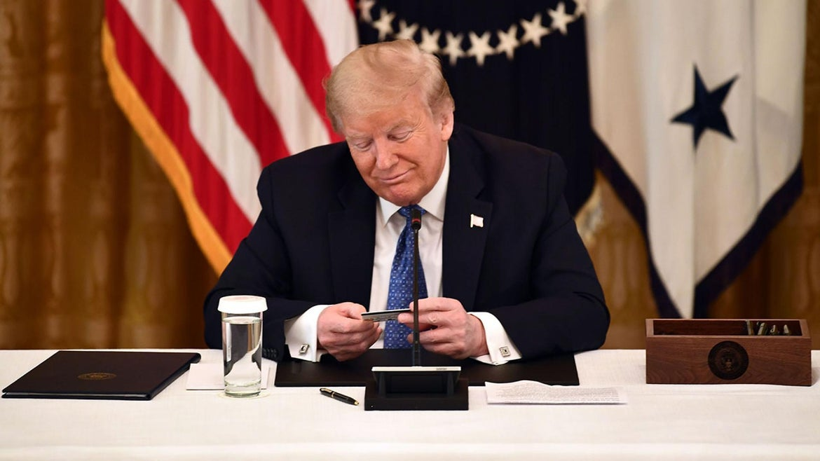 US President Donald Trump looks at a pre-paid debit card during a meeting with his cabinet on May 19, 2020.