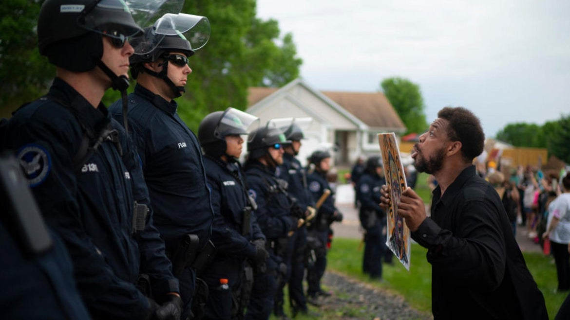A demonstrator holding a sign jumped up and down so police officers behind the front lines could see it. Demonstrators protested the killing of George Floyd outside the Oakdale home of fired Minneapolis Police Officer Derek Chauvin.(Photo