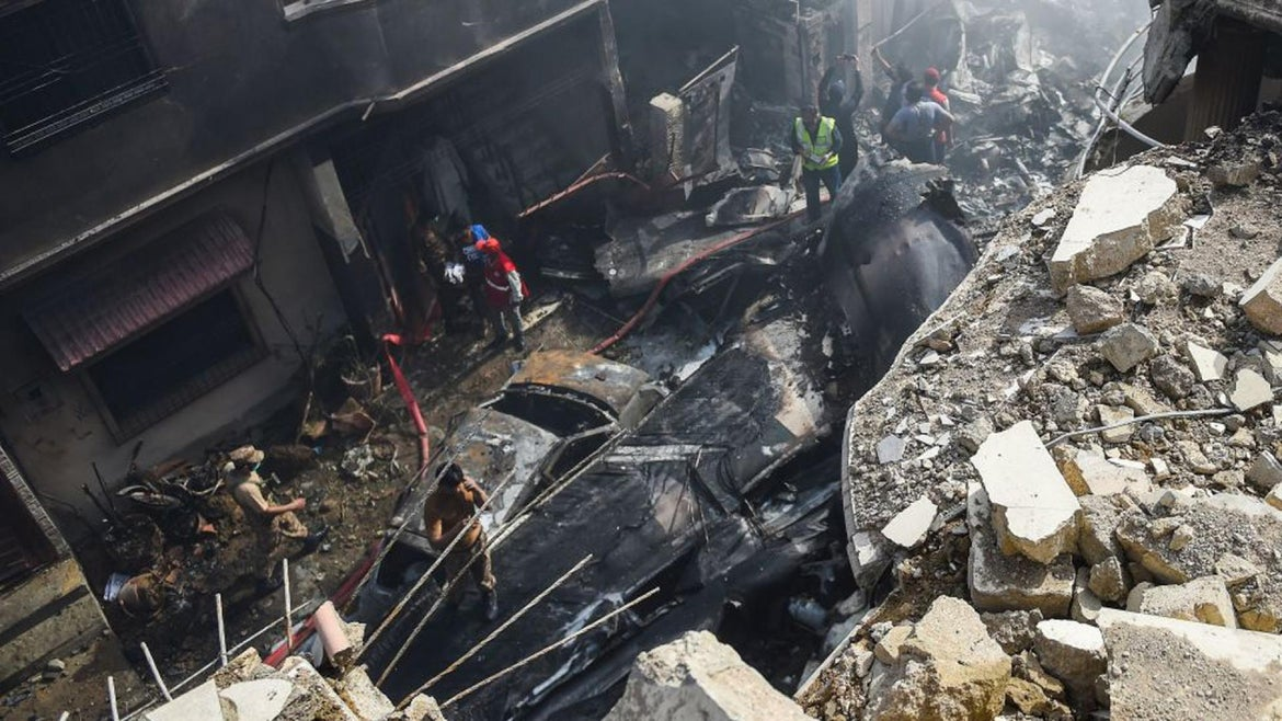 Rescue workers gather at the site after a Pakistan International Airlines aircraft crashed in a residential area in Karachi on May 22, 2020.