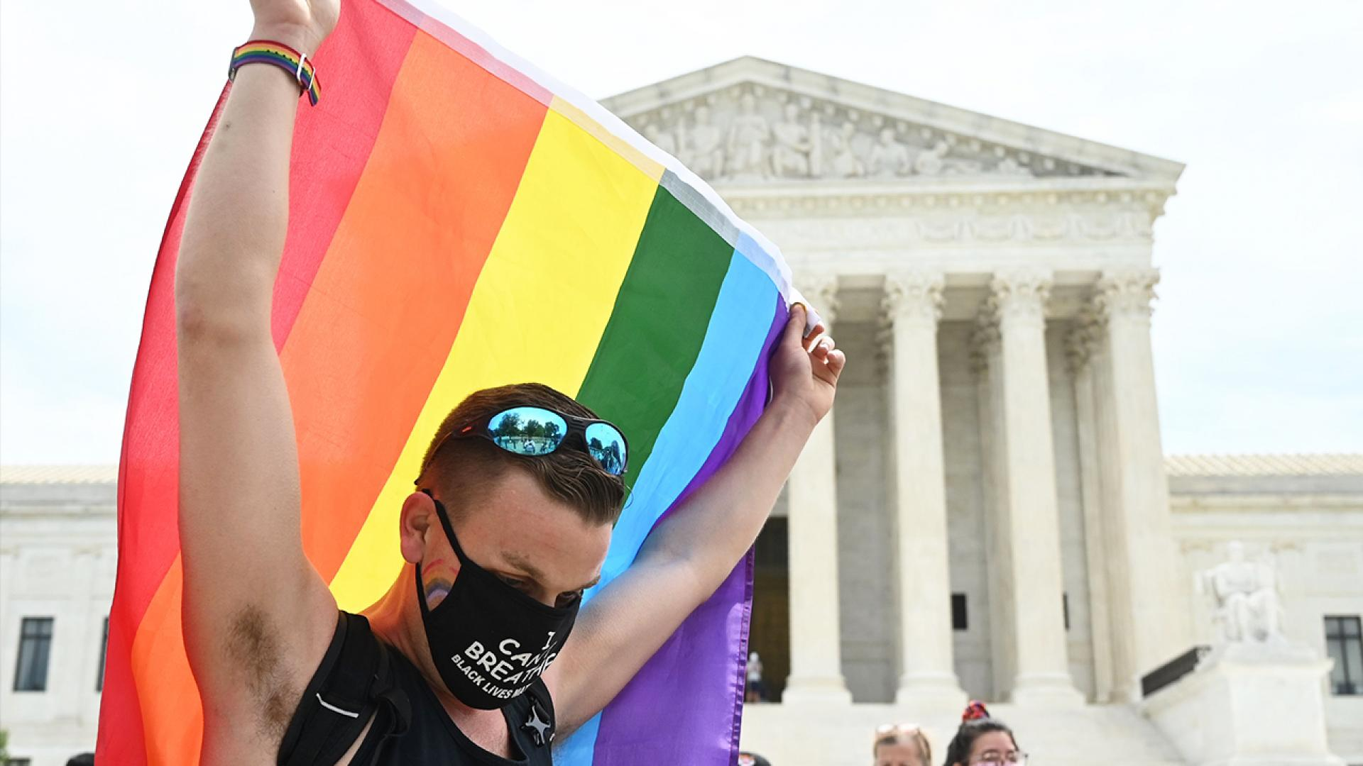 A man waves a rainbow flag in front of the U.S. Supreme Court in light of the ruling.