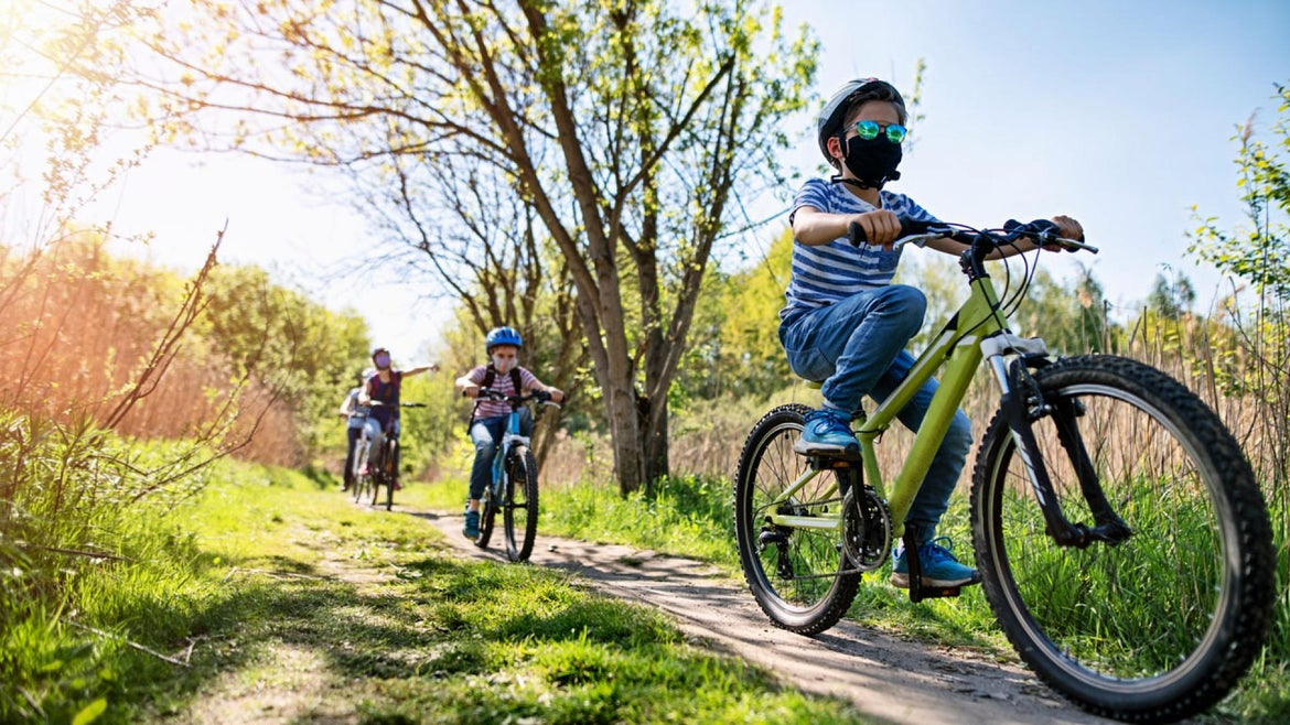 Mother and kids are enjoying a bike trip together during the COVID-19 pandemic.