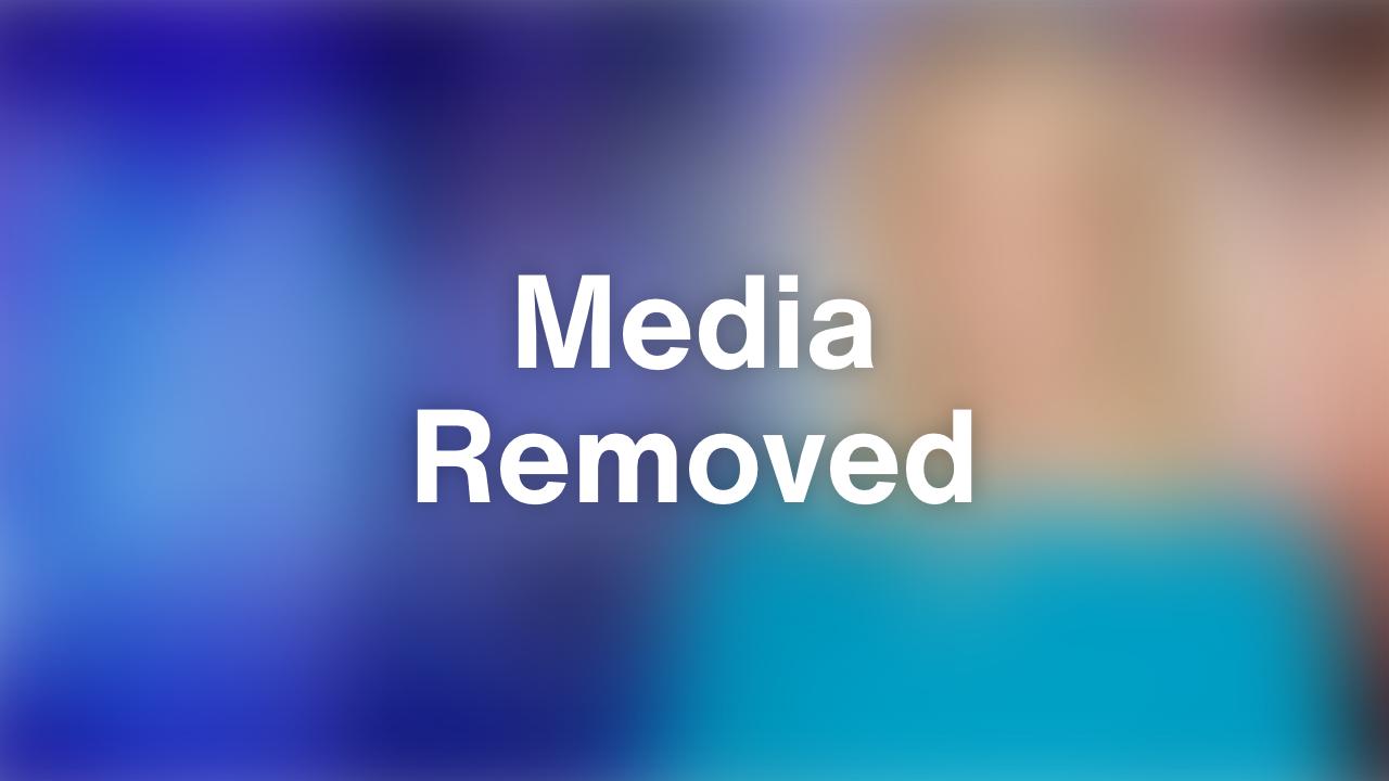 A Black man successfully hangs George Floyd art over traffic light.