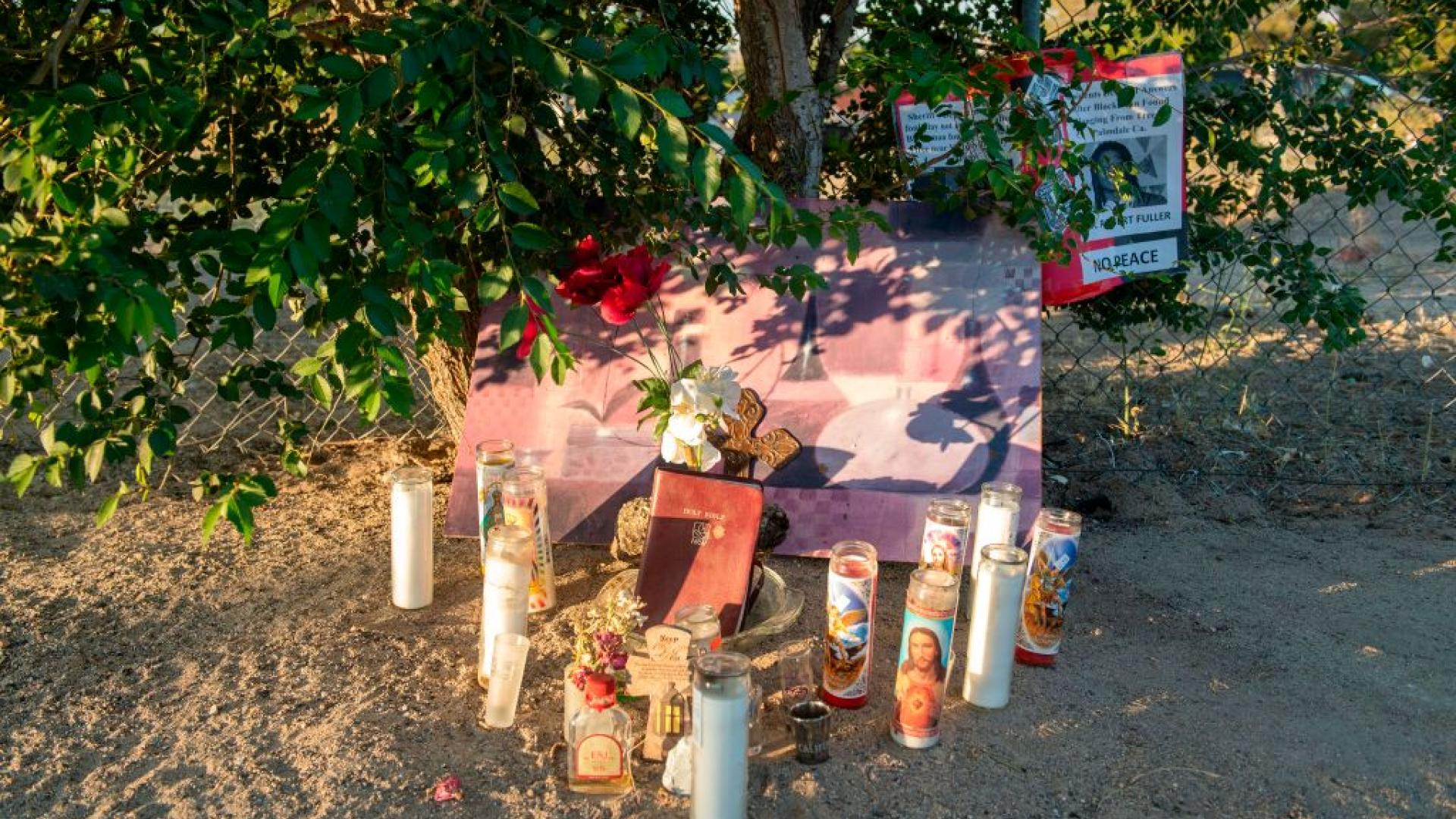 Candles at memorial for Malcolm Harsch, whose body was found hanging from a branch.