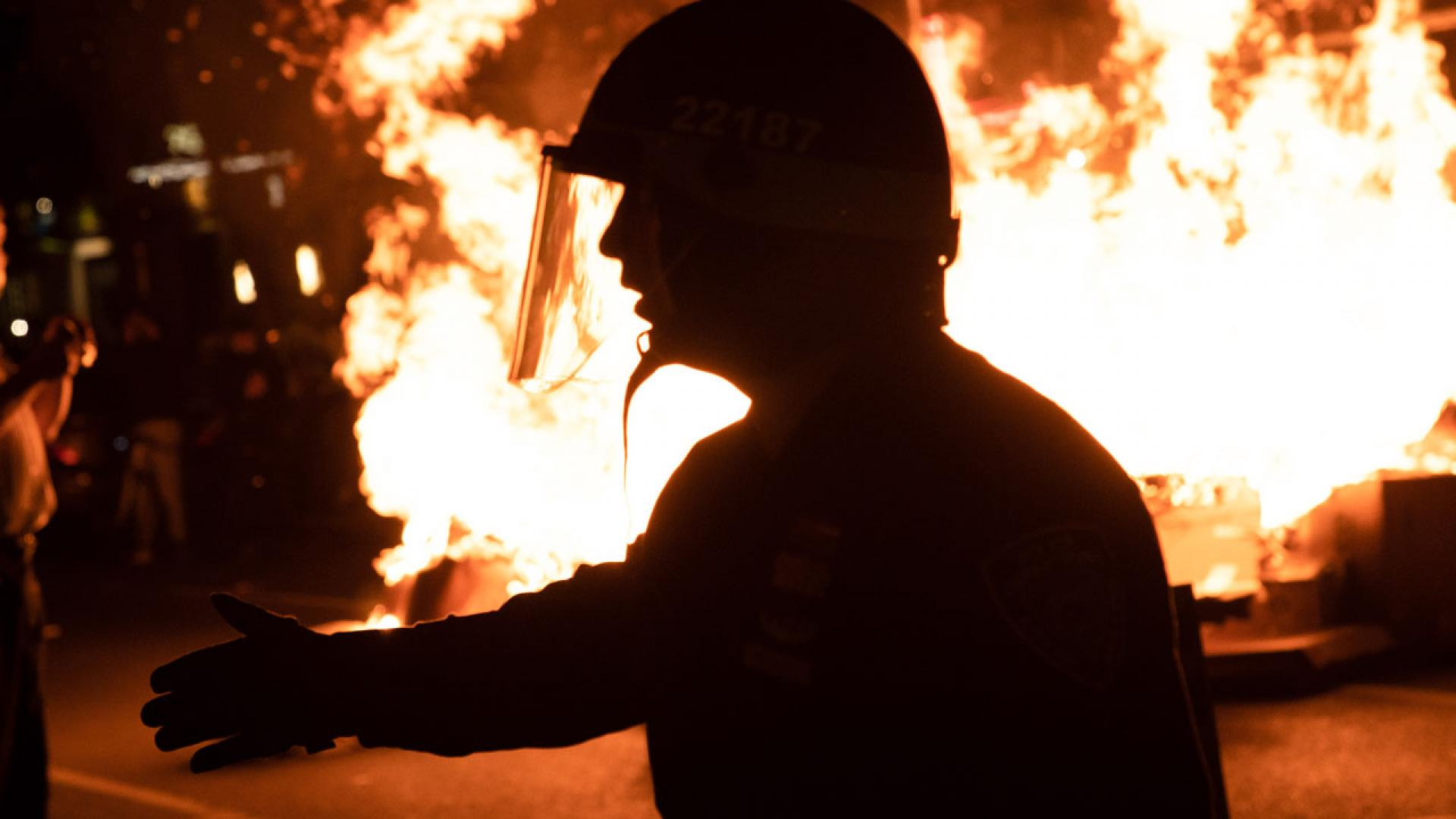 A police officer stands in front of a fire amid protests in Brooklyn, New York.