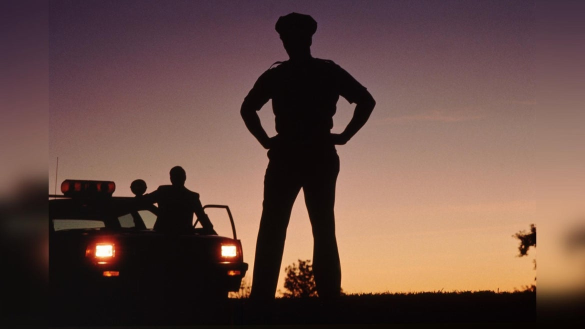 Silhouette of policemen with police car in background