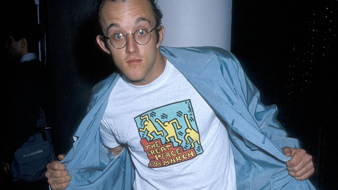Keith Haring showing off one of his t-shirts with his art.