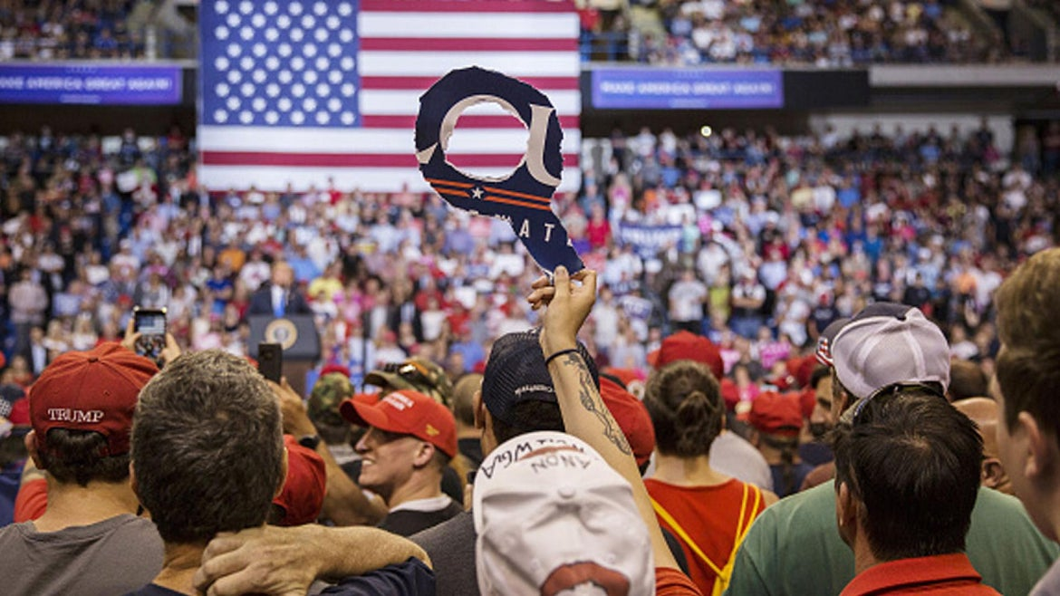 """An attendee holds a sign of the letter """"Q"""" as U.S. President Donald Trump addresses the crowd during a rally"""