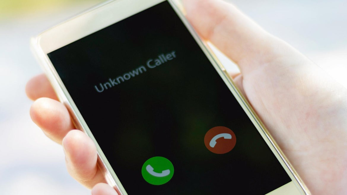 Person receives call their phone has flagged a possible spam caller.