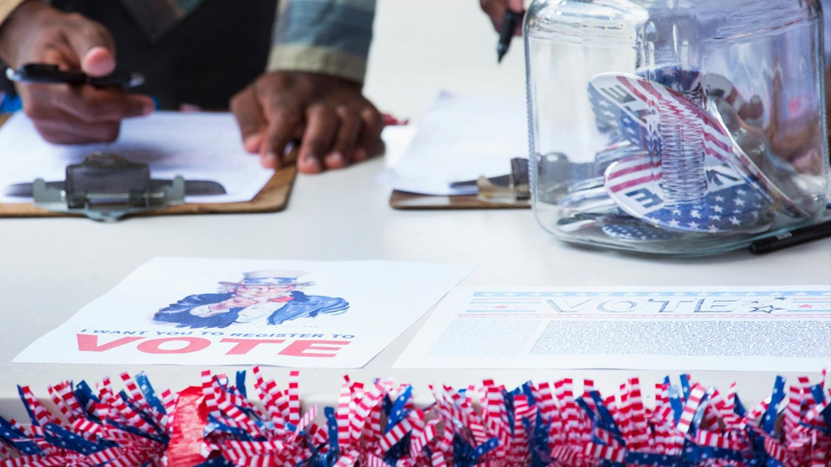 A person hands a pen to someone at a table with voting stickers.