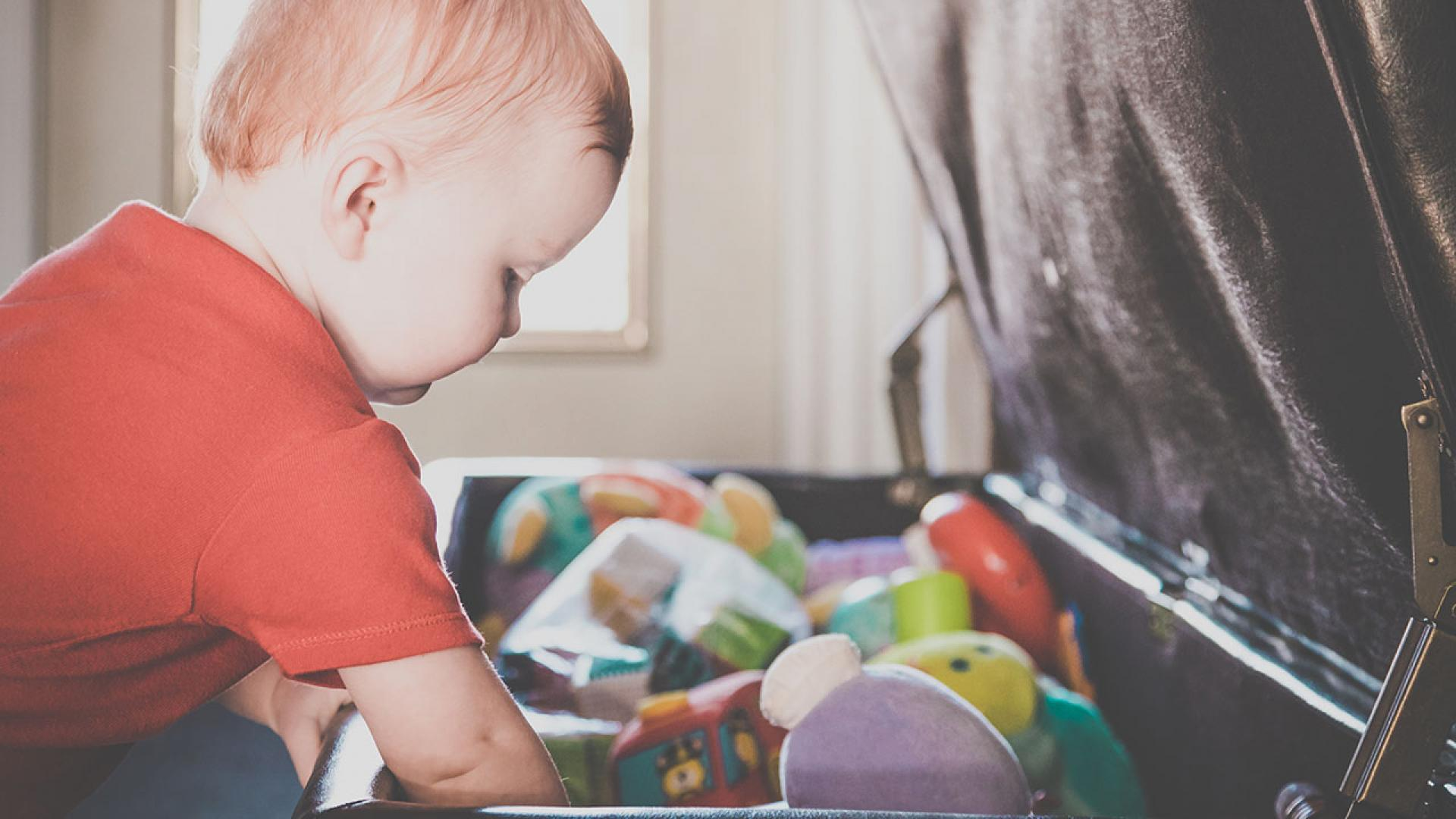 Baby Boy Exploring and Looking Inside a full Toy Box
