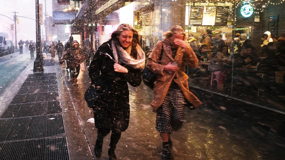 People caught on the streets dashed for cover as the snow squall hit New York City on Wednesday.
