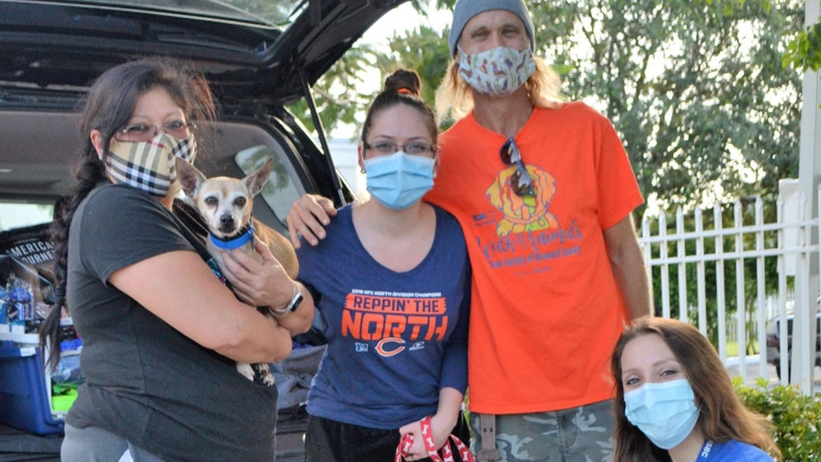 Vasquez Family holding King with Humane Society of Broward County staffer.