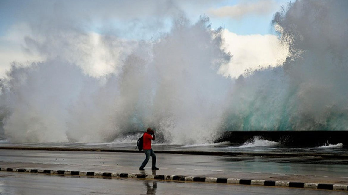 A photographer takes pictures as the sea pounds against Havana's seawall, the Malecon, on Nov. 9, 2020 after the passage of Tropical Storm Eta