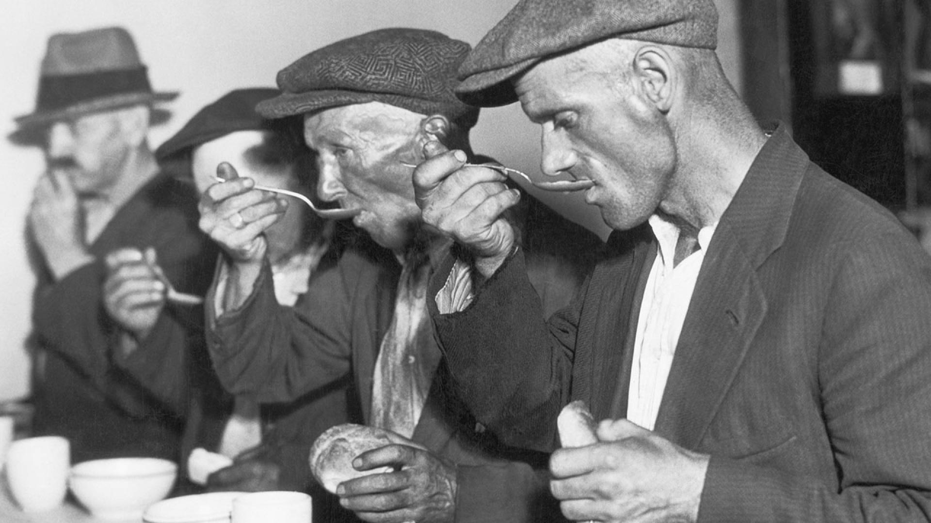 The Great Depression in the U.S.: Men eating bread and soup in a breadline.