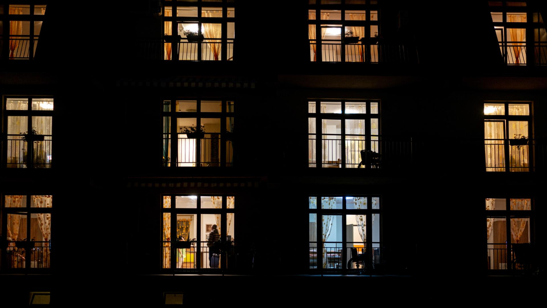 Illuminated windows of night house with people inside - stock photo