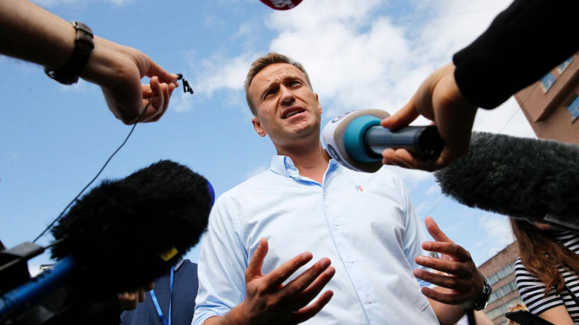 Russian opposition leader Alexei Navalny speaks with journalists during a rally