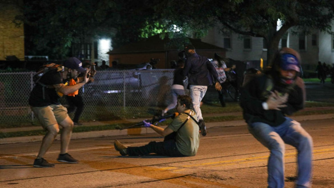 A man (R) was shot in the chest as clashes between protesters and armed civilians who protect the streets of Kenosha