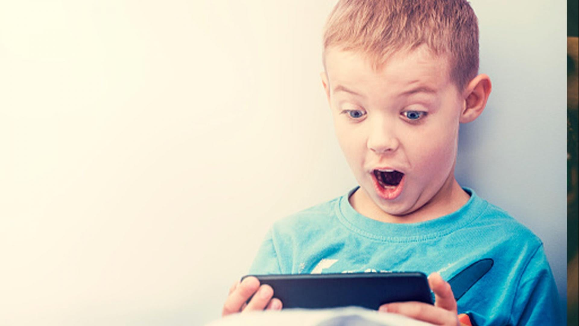 A stock photo of a young boy playing a video game on his ipad.