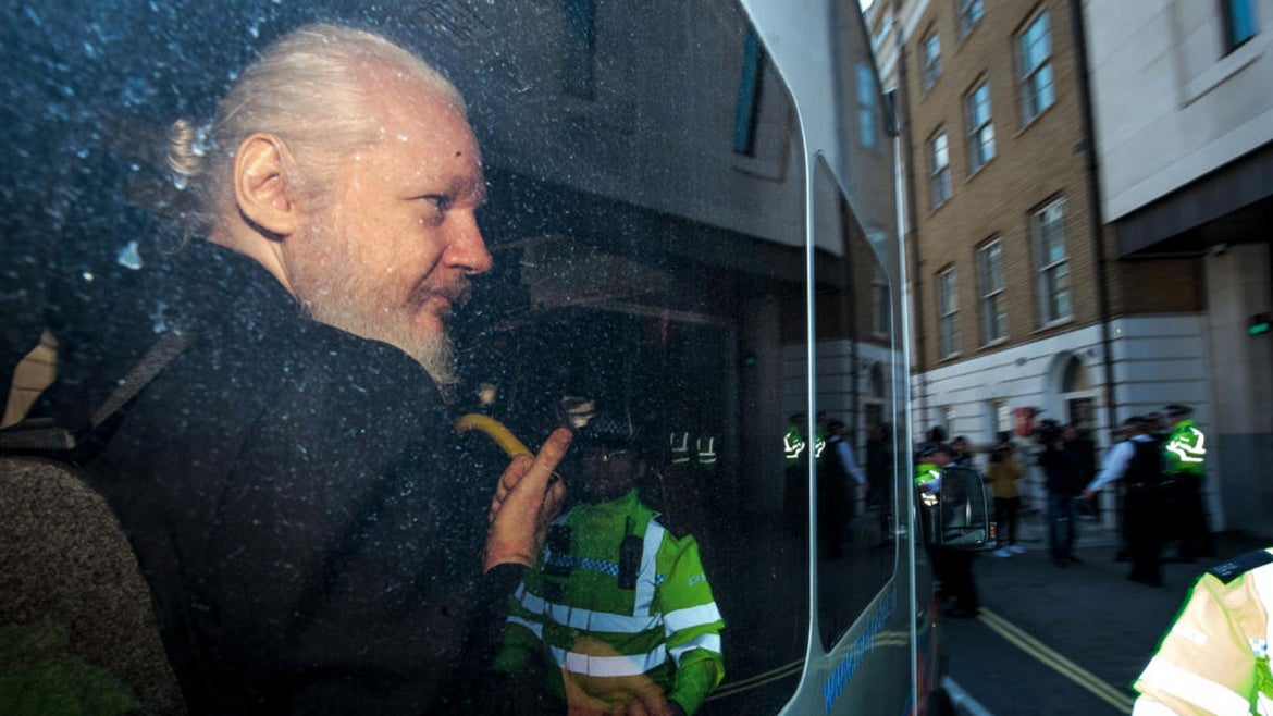 Julian Assange gestures to the media from a police vehicle on his arrival at Westminster Magistrates court on April 11, 2019