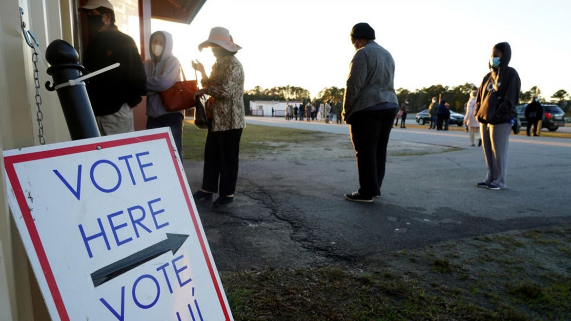 Voters stand in line to cast their ballots during the first day of early voting in Georgia