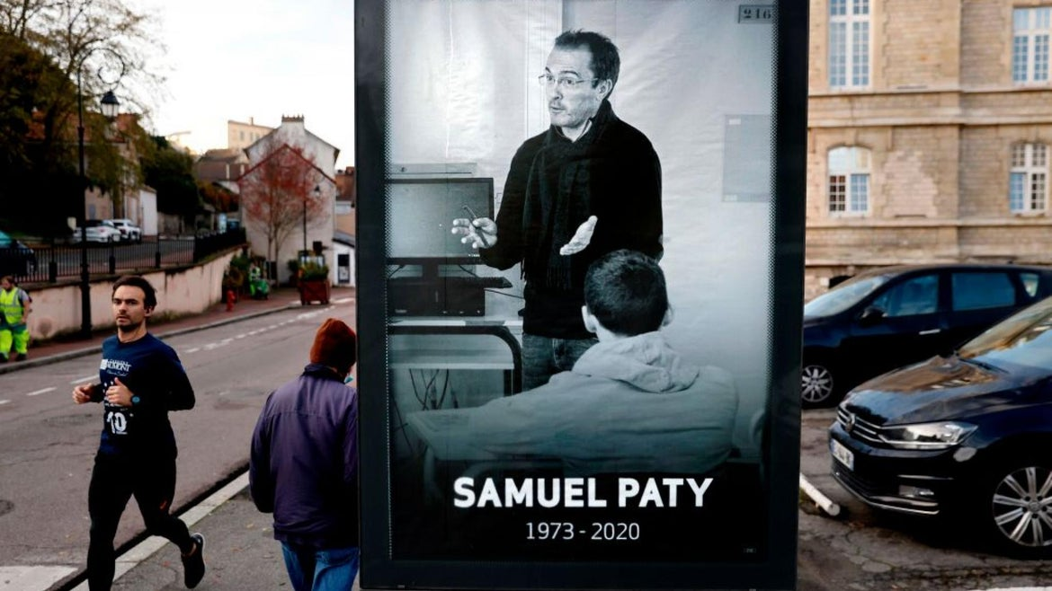 Pedestrians pass by a poster depicting French teacher Samuel Paty placed in the city center of Conflans-Sainte-Honorine, 30kms northwest of Paris, on November 3, 2020