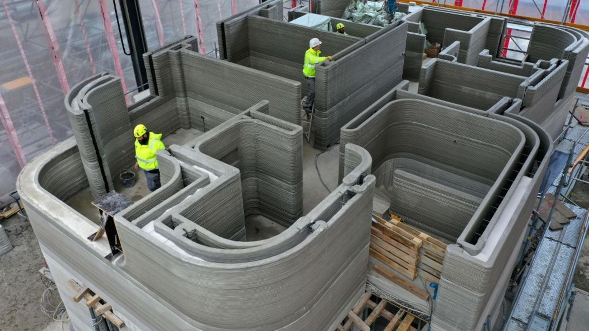 An aerial view shows construction workers standing in the scaffolded construction site of a house, where several layers of concrete have already been applied by a 3D printer, and the next printing stage is already underway, in Beckum, western Germany, on November 26, 2020.