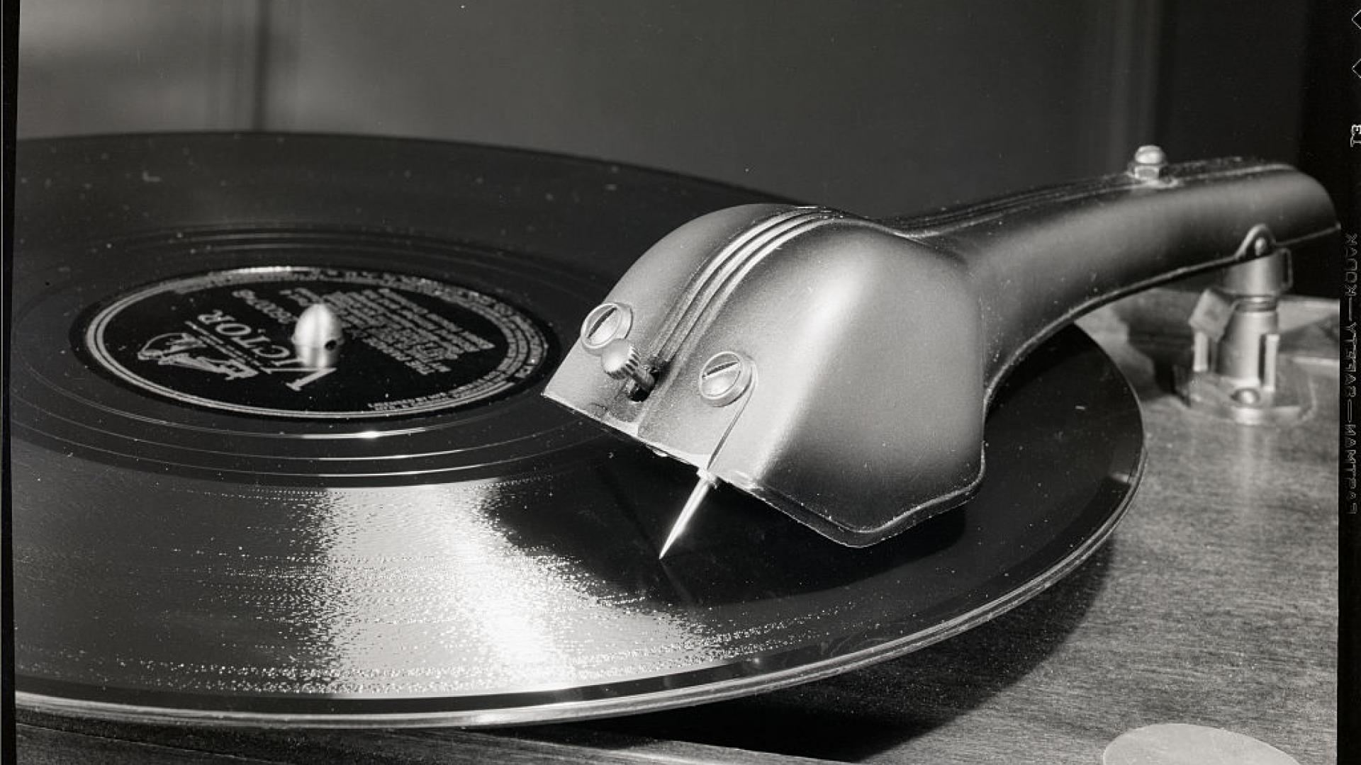 Close-up of a phonograph needle and arm on a record.