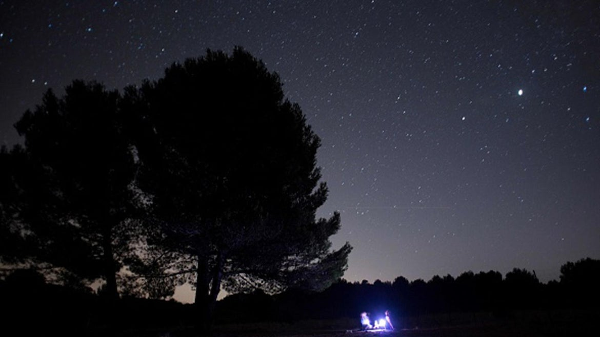 A couple look at meteor streaks across the sky against a field of stars during a meteorite shower in Ronda late on August 11, 2020