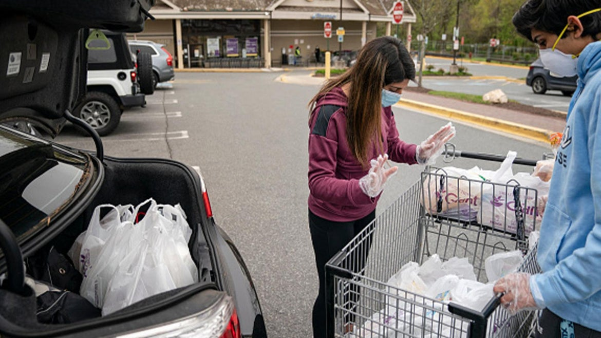 Volunteers shopping for groceries to drop off for those in need.