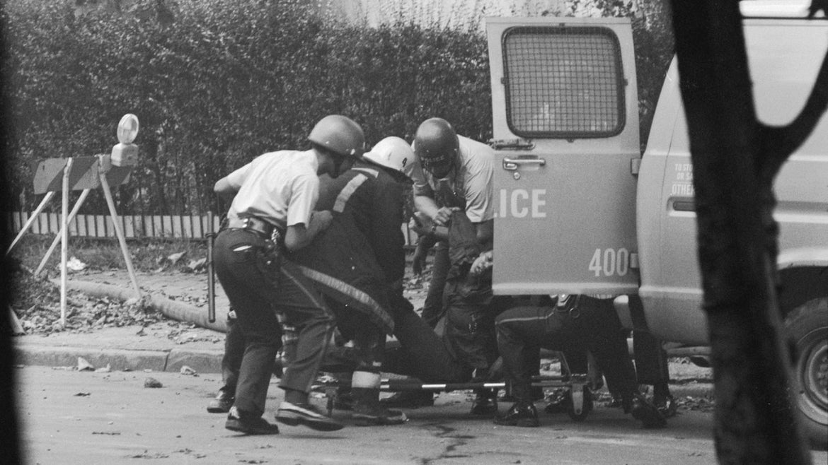 Police officers place injured people into a police van after an attack on the MOVE cult headquarters in the Powelton Village section of Philadelphia, Pennsylvania