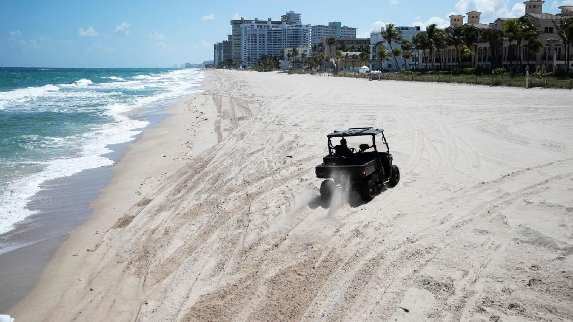 A Lauderdale-by-the-Sea police officer drives along an empty beach as the effort to stop the coronavirus pandemic continues on March 20, 2020 in Pompano Beach, Florida.