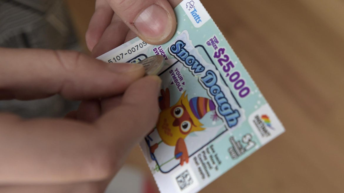 A Tatts Group Ltd. Instant Scratch-It scratchcard is arranged for a photograph at a newsagent's store in Melbourne