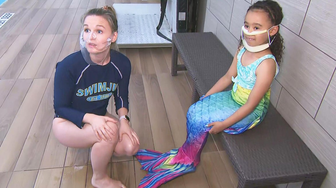 7-year-old Julia Cramer, an experienced swimmer, tries out the mermaid tail bathing suit under the supervision of a swim instructor.